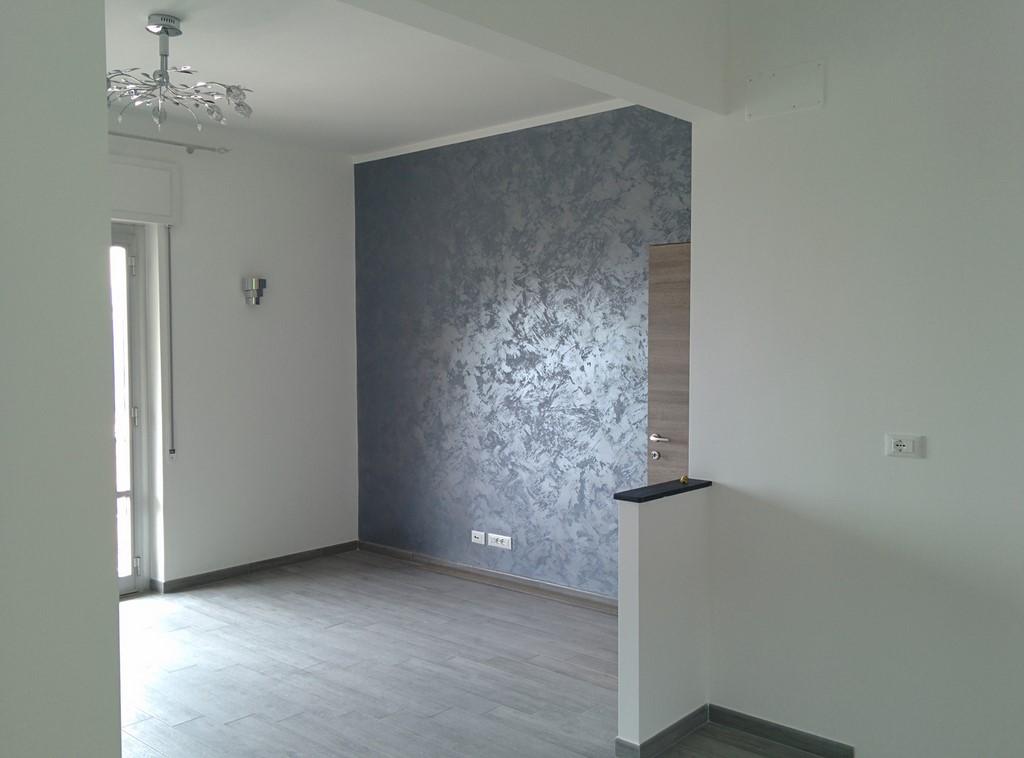 salotto con parete tinteggiata con riflessi argento