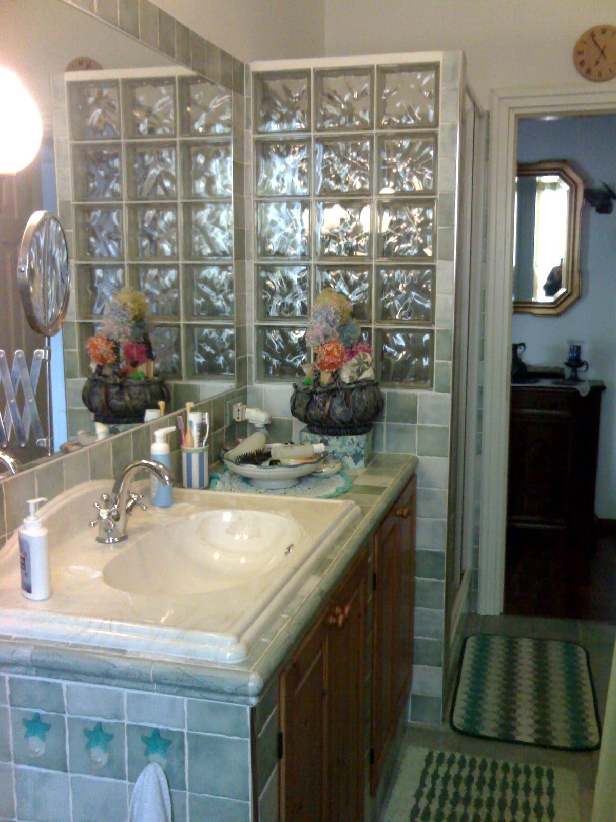 Bagno con lavandino in muratura e parete doccia in vetrocemento